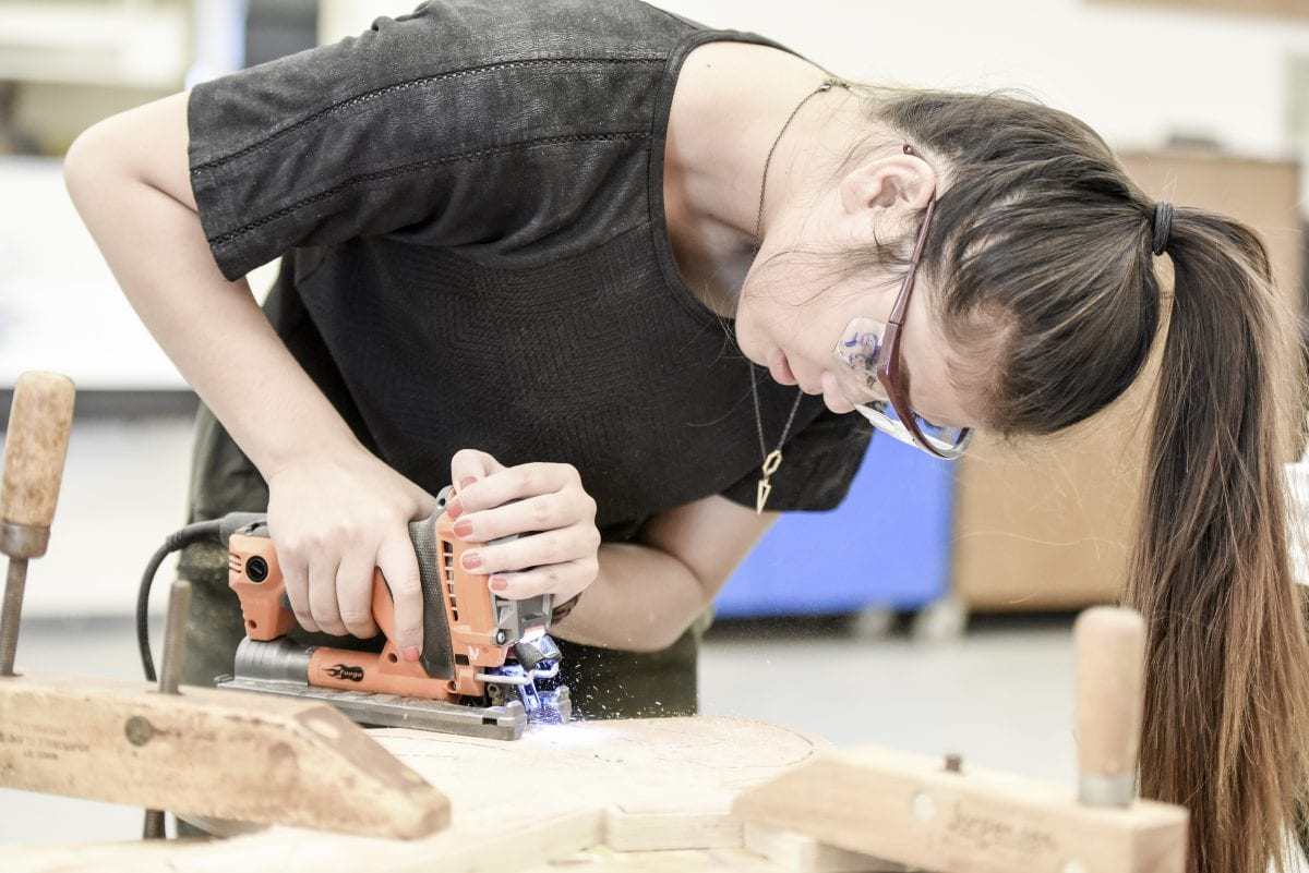 Student working with a power tool on woodwork