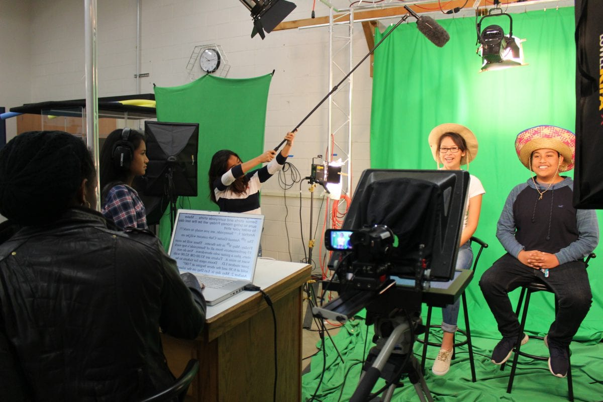 Two students filming in front of a green screen