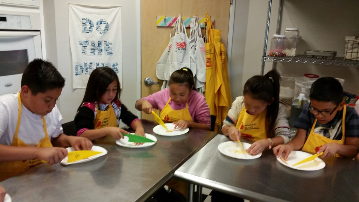 Young Chef's Academy students prepare ingredients with safety knives